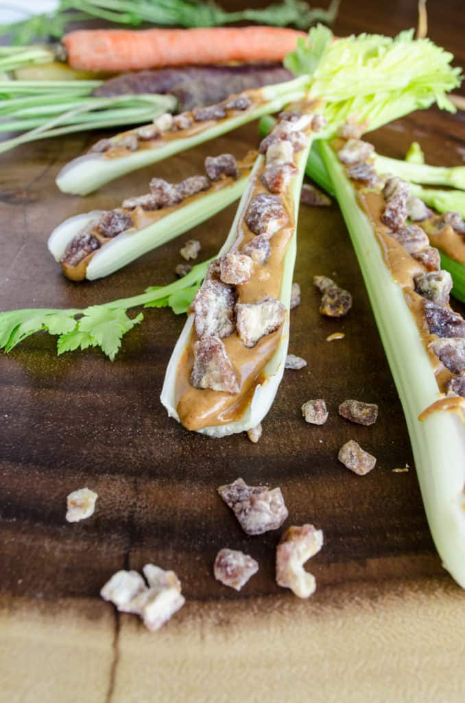 A closeup picture of a celery stick with leaves still attached at one end, filled with peanut butter and dried dates to make Ants on a Log.