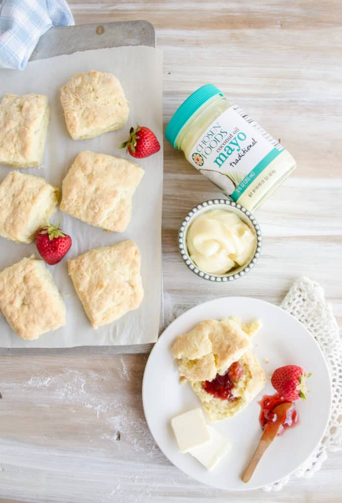 Quick Fluffy Coconut Biscuits sit on a baking sheet and a plate with strawberry jam.