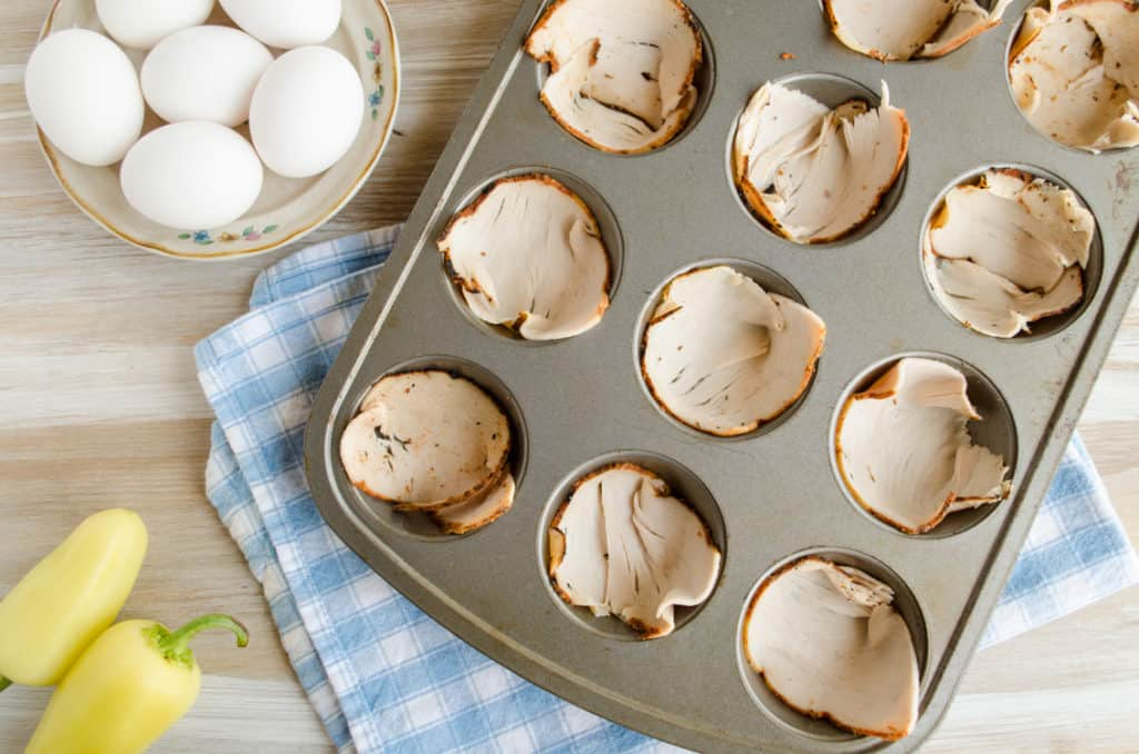 A muffin tin sits ready to be filled with the ingredients for Green Chile Turkey Breakfast Cups.