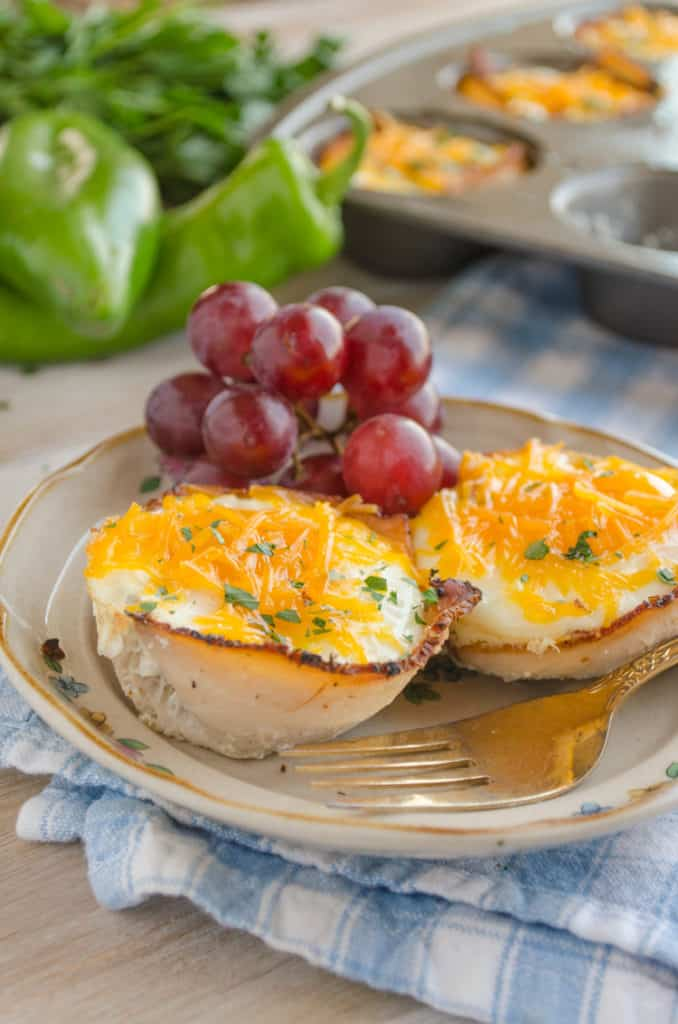 Two Green Chile Turkey Breakfast Cups sit on a plate garnished with red grapes.