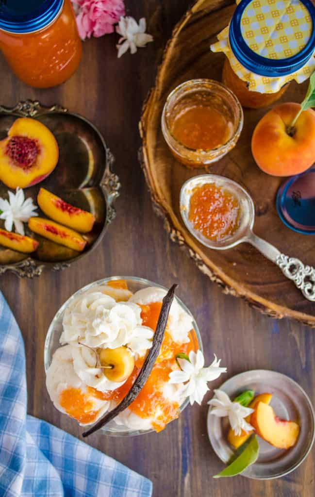 View looking down at a table dressed with Homemade Vanilla Bean Peach Jam drizzled over ice cream.
