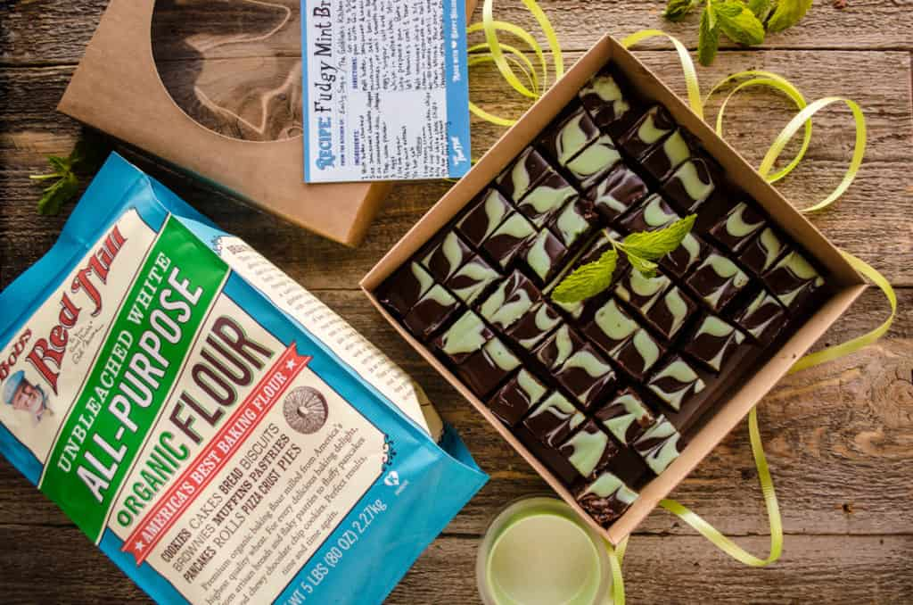 Fudgy Mint Brownies in a gift box with the top off next to a bag of Bob's Red Mill All-Purpose Organic Flour.