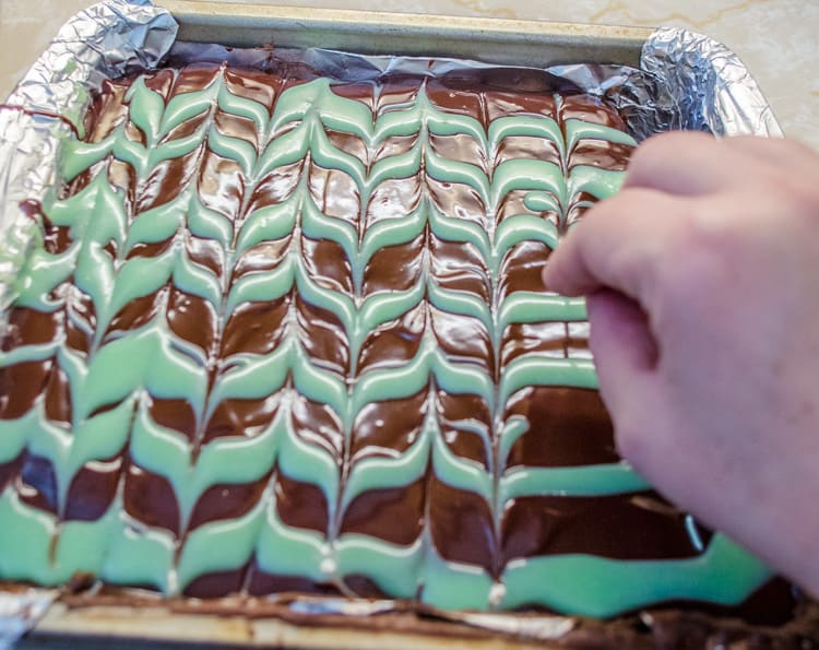 A toothpick is drawn through layers of white mint chocolate and semisweet chocolate to make a pretty chevron pattern on Fudgy Mint Brownies.