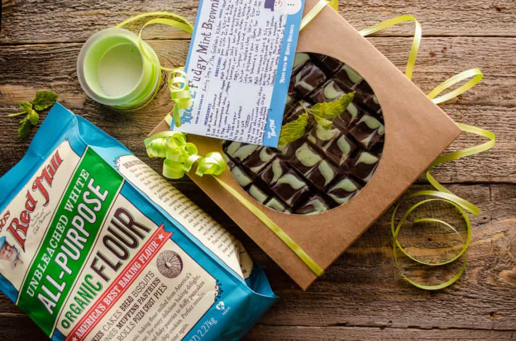 Fudgy Mint Brownies packaged in a gift box tied with a green curly ribbon bow. A recipe card sits on top.