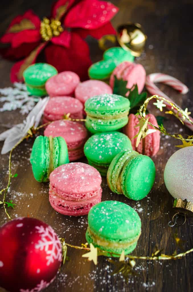 A closeup of red and green Christmas Macarons surrounded with Christmas Decorations and poinsetta leaves.