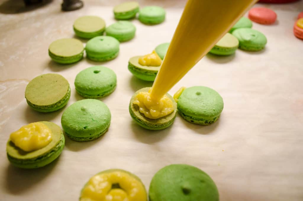 Filling being piped into Christmas Macarons.