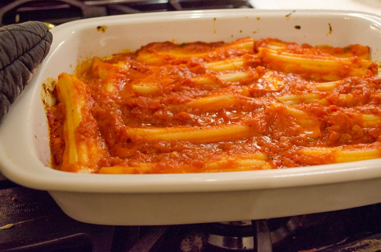 A baking dish filled with stuffed manicotti is smothered in marinara sauce for Meatless Monday Cheese Stuffed Manicotti.