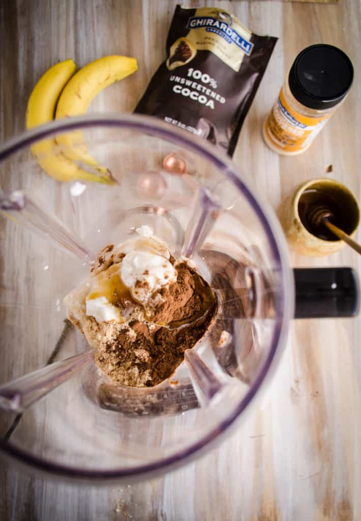 A top down view of the ingredients for a Peanut Butter Chocolate Banana Smoothie sit in a blender ready to be blended.