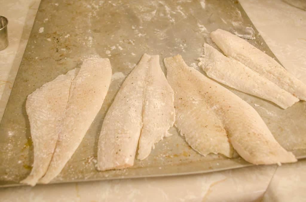 A baking sheet with breaded raw fish ready to be made into Fast Fish Dinner with Herbed Browned Butter.