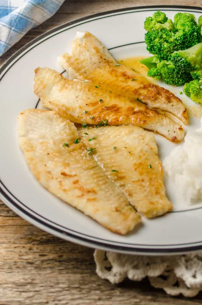A plate of Fast Fish Dinner with Herbed Browned Butter sits with sides of rice and steamed broccoli.