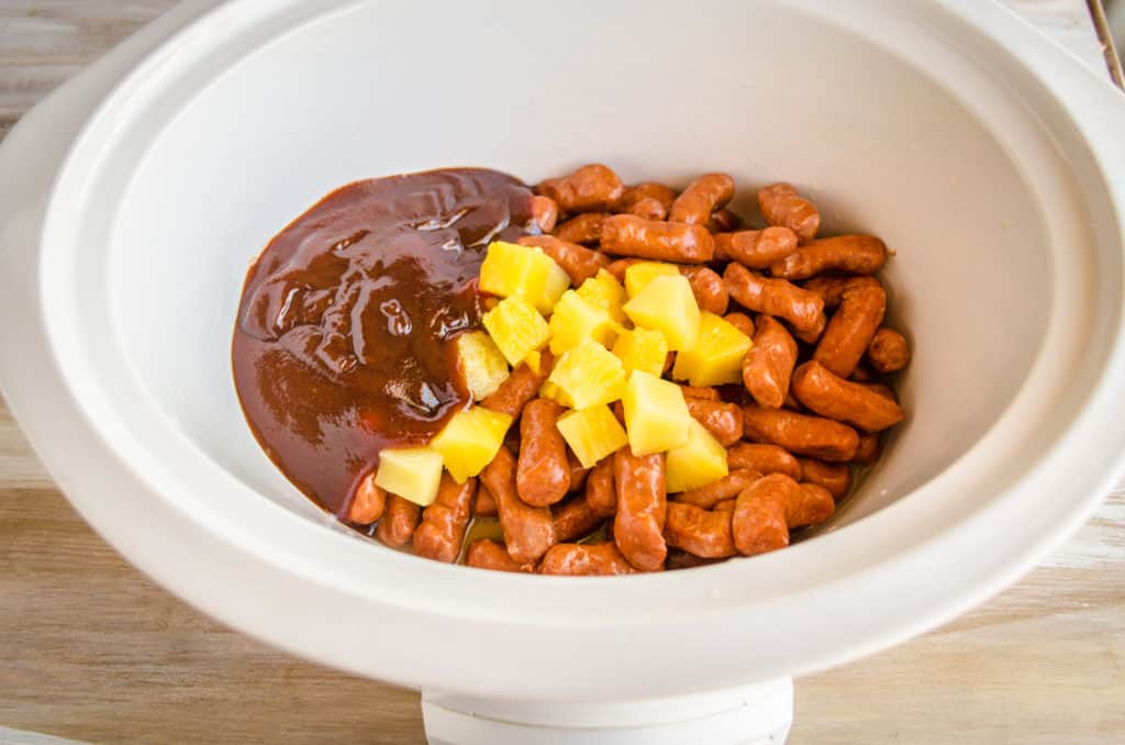 A slow cooker is filled with Lit'l smokies, pineapple chunks and barbecue sauce ready to cook into Slow Cooker Hawaiian Little Smokies - The Goldilocks Kitchen