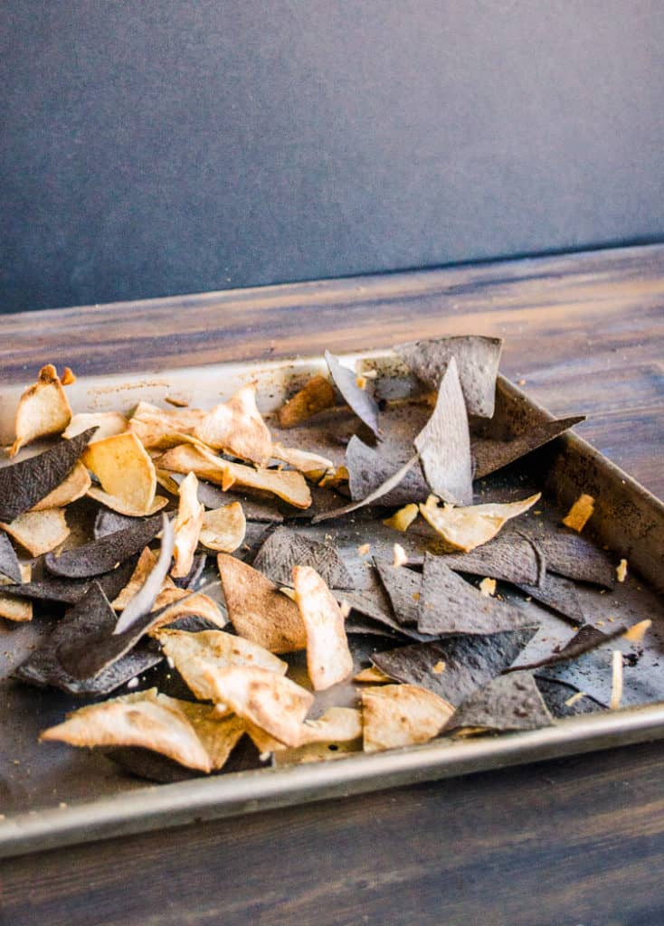 A baking sheet sits on a table full of yellow and blue corn Crispy Baked Southwestern Tortilla Chips. - The Goldilocks Kitchen