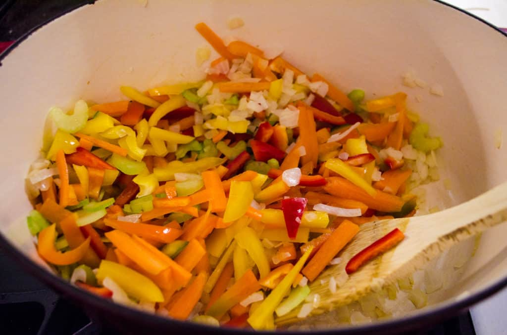 Chopped celery, bell pepper, onion, garlic and carrot are being cooked in a stovetop dutch oven for Meatless Monday Vegetable Rotini Soup.