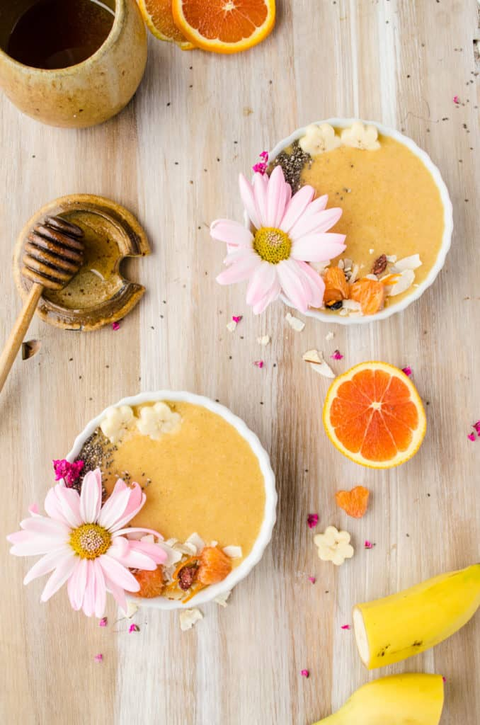 Two Cold Buster Smoothie Bowls sit on a wooden tables surrounded by fresh fruit and bits of coconut and flowers.