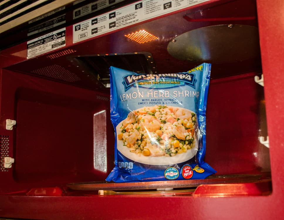 Van de Kamp's Seafood and Veggie Meals for Fish on Friday - Lemon Herb Shrimp with Chickpeas, Sweet Potatoes, and Spinach sits in a microwave ready to be cooked - The Goldilocks Kitchen