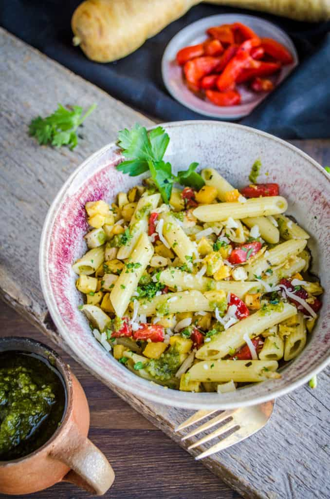 A bowl of Pesto Pasta with Roasted Root Veggies sits on a wooden plank, surrounded by fresh ingredients.