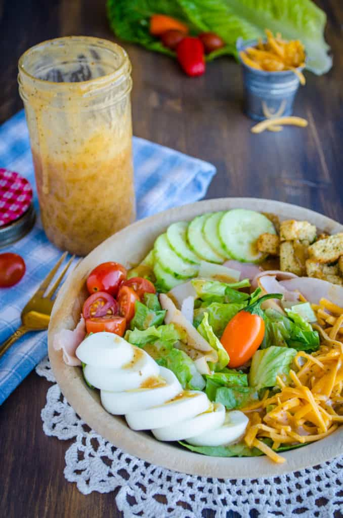 A chef's salad drizzled with Ten Dollar Dressing sits in a wooden bowl with the dressing jar just behind it. - The Goldilocks Kitchen