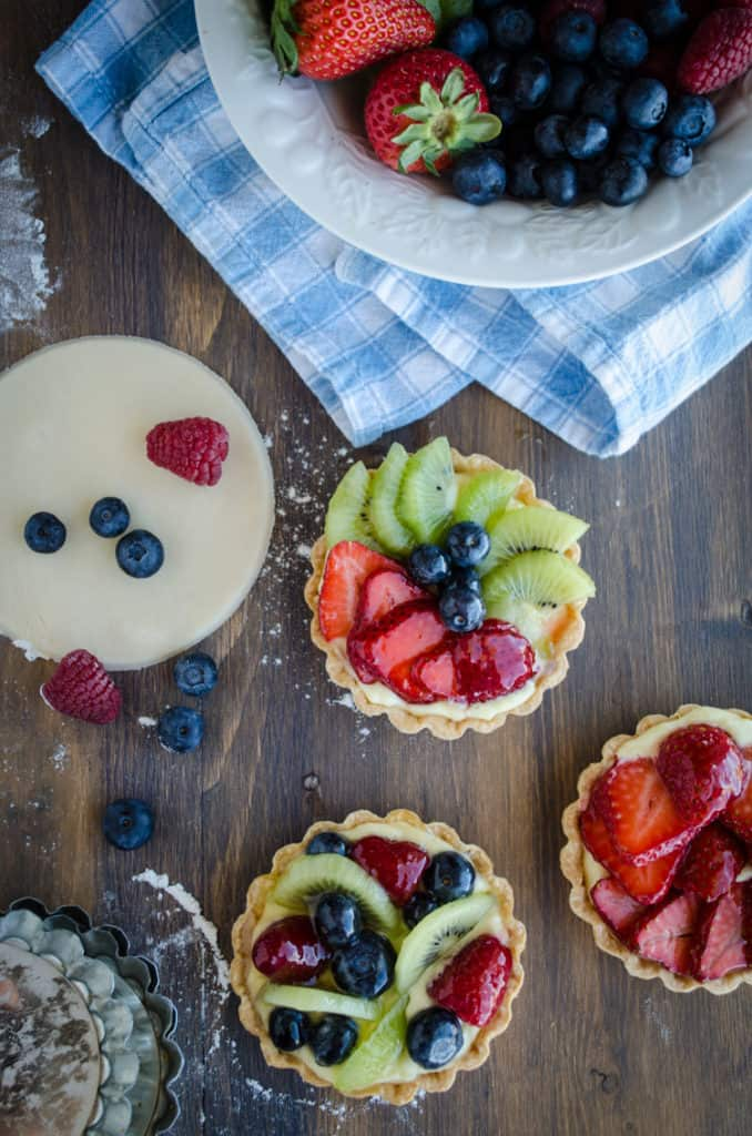 Fruit Tartlets sit on a table surrounded by berries, pie dough and empty tartlet pans - The Goldilocks Kitchen