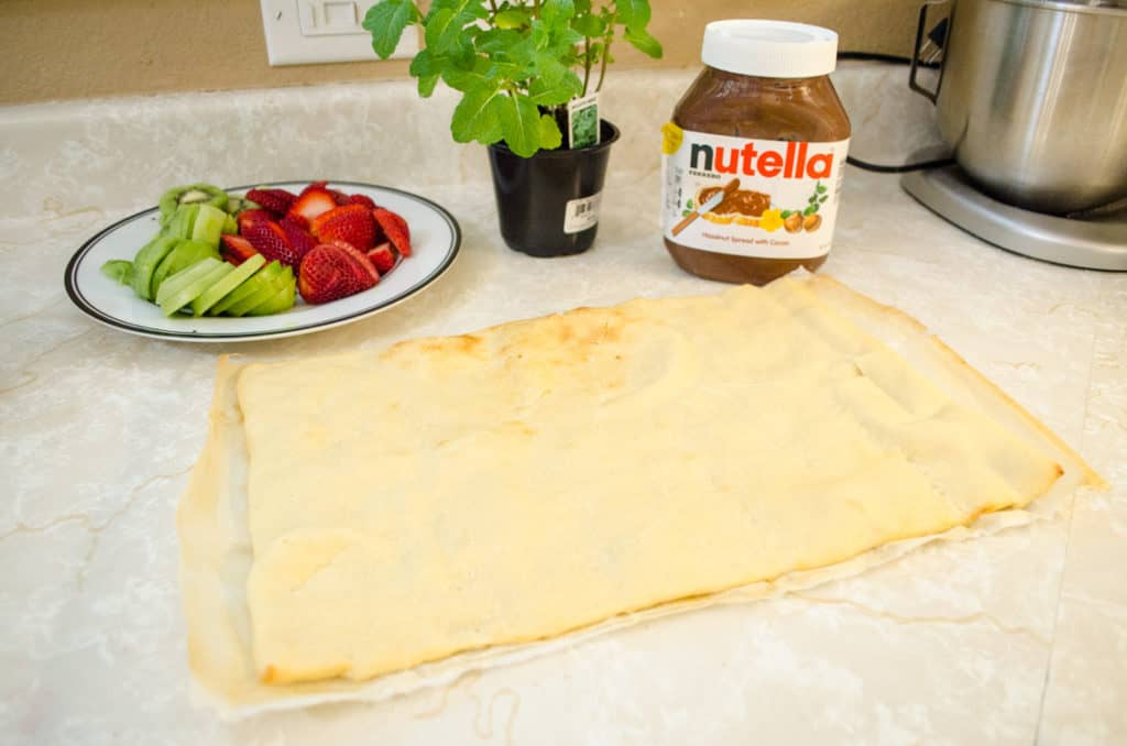 A plate of freshly sliced strawberries and kiwi's, a jar of Nutella and a rectangular cooked pizza crust sit on the counter ready to be turned into Nutella Pizza - The Goldilocks Kitchen