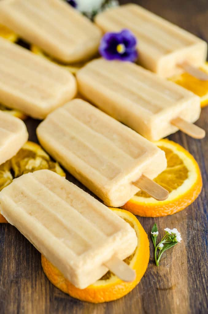 Orange Creamsicle Smoothie Pops sit on slices of oranges surrounded by white and purple flowers - The Goldilocks Kitchen