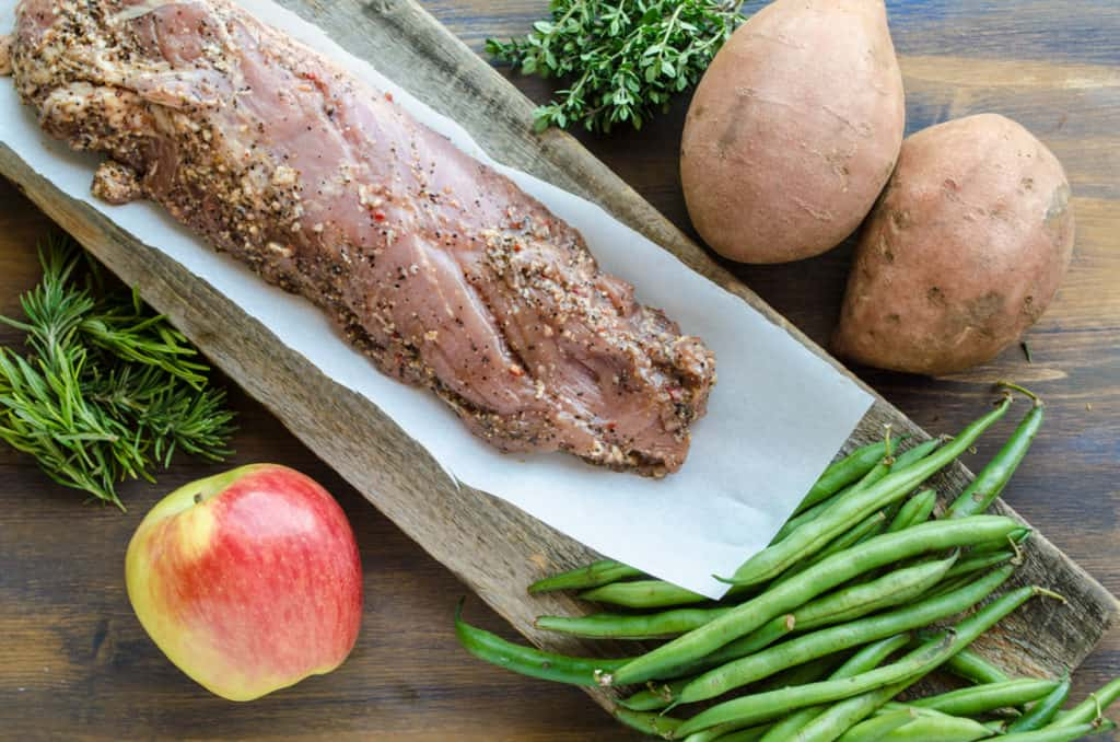 All the raw ingredients displayed to make Roasted Pork Apple Sweet Potato Dinner; pork tenderloin, green beans, an apple, two sweet potatoes, fresh thyme and rosemary - The Goldilocks Kitchen