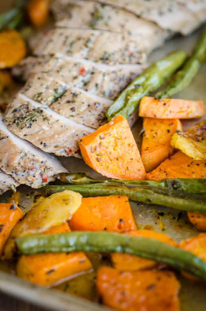 A close up of beautifully herb seasoned sliced pork tenderloin surrounded by brightly roasted vegetables for Roasted Pork Apple Sweet Potato Dinner - The Goldilocks Kitchen