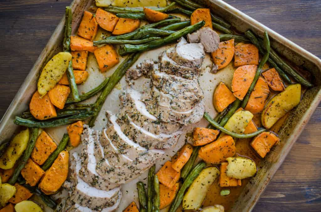 Roasted Pork Apple Sweet Potato Dinner sits in a sheet pan on a wooden tabletop with the pork surrounded by the other ingredients - The Goldilocks Kitchen