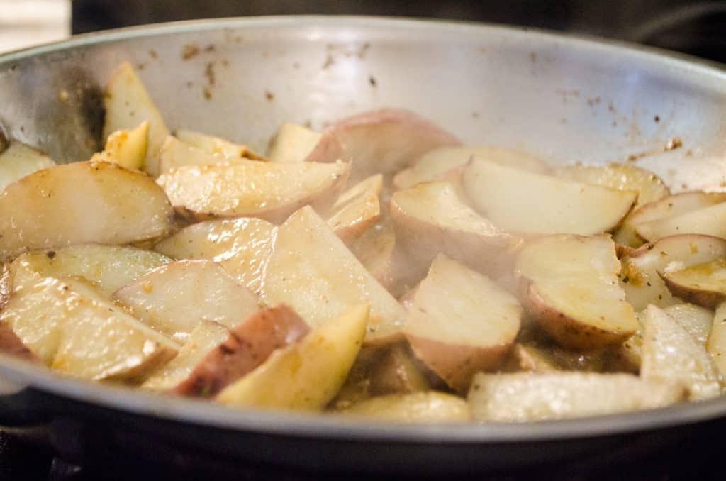 Red potato wedges are cooked in a skillet for Weeknight Roasted Chicken Breast with Red Potatoes- The Goldilocks Kitchen