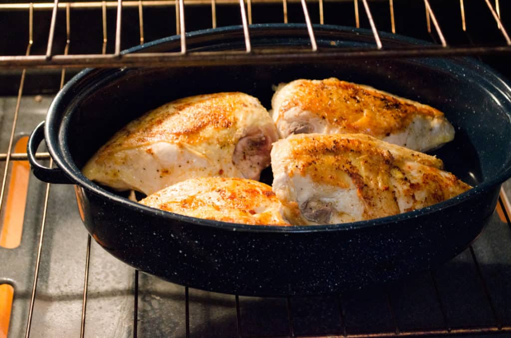 Golden browned chicken breast is nestled into a roasting pan skin side up, in an oven for Weeknight Roasted Chicken Breast with Red Potatoes - The Goldilocks Kitchen