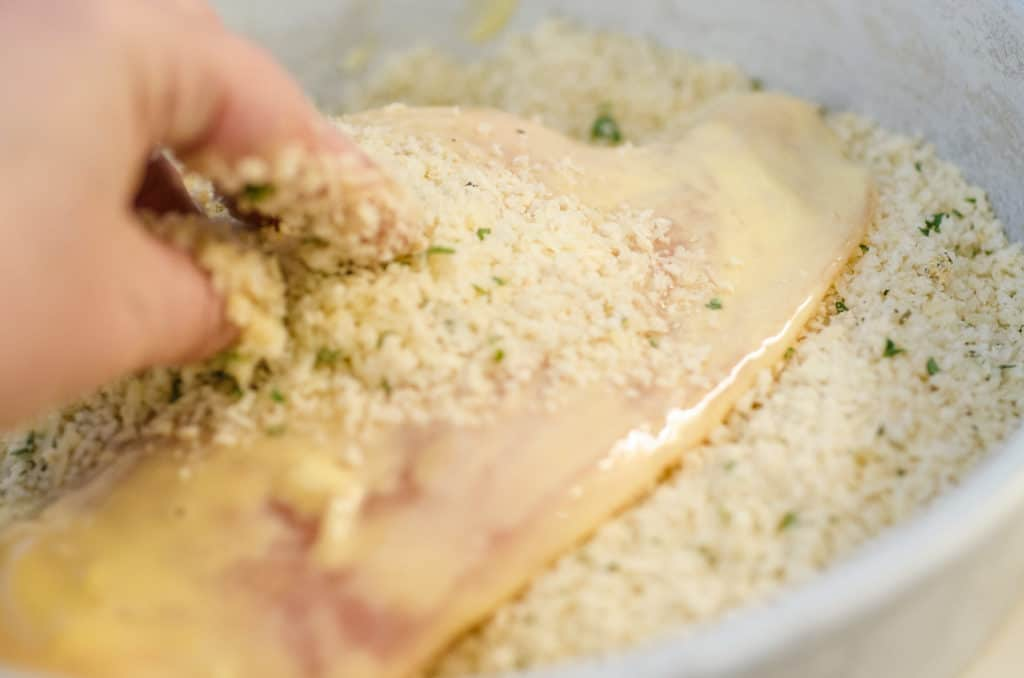 A chicken cutlet is pressed into a mixture of parmesan cheese and seasoned bread crumbs to make Easy Chicken Parmesan.