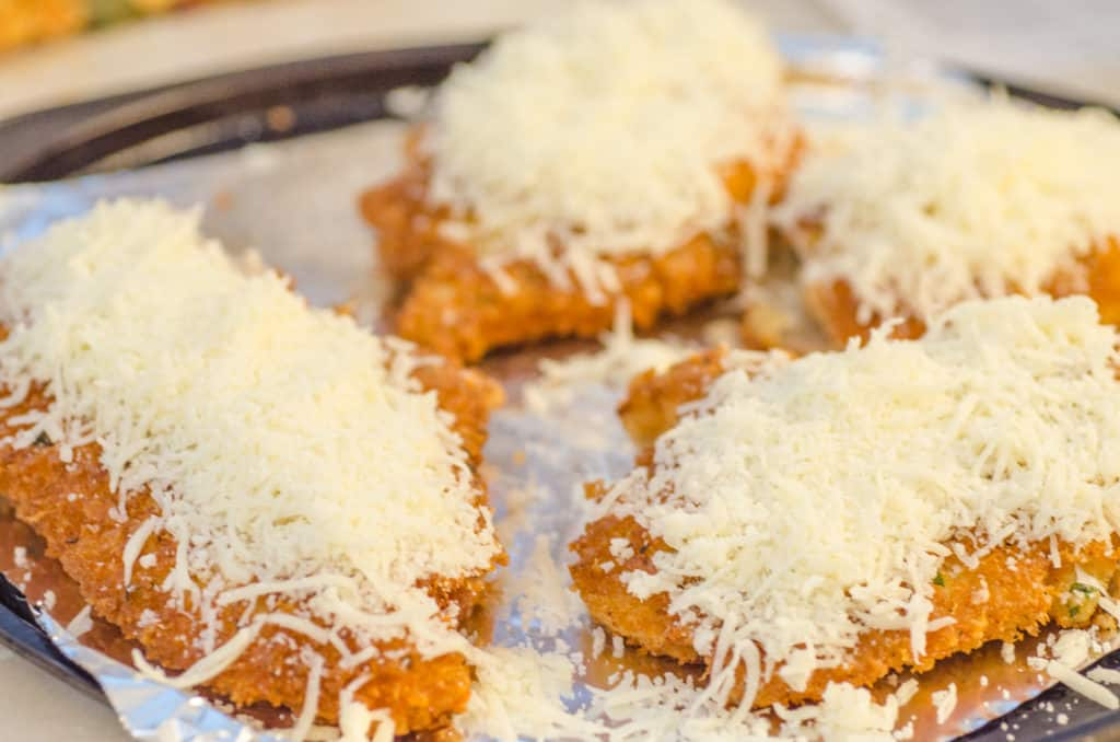 Freshly fried Easy Chicken Parmesan pieces are topped with mozzarella cheese and broiled to melt it.