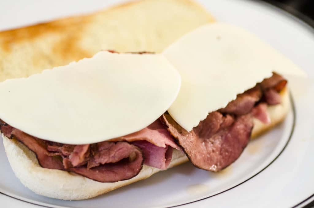 A French Dip with Au Jus sandwich is topped with two torn pieces of provolone cheese that is waiting to be melted.
