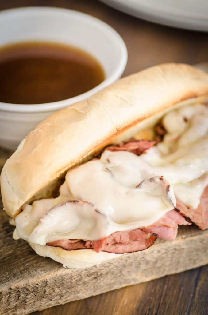 A fresh made French Dip with Au Jus sandwich sits next to a small cup of au jus.