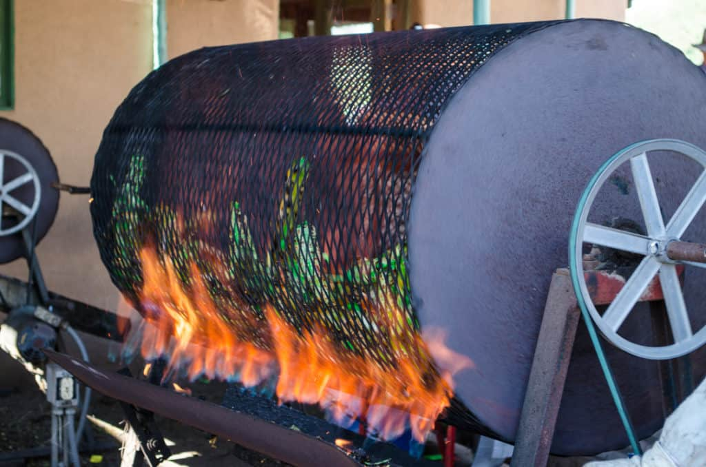 Green chile roasting in a barrel roaster for New Mexico Green Chile Roasting 101