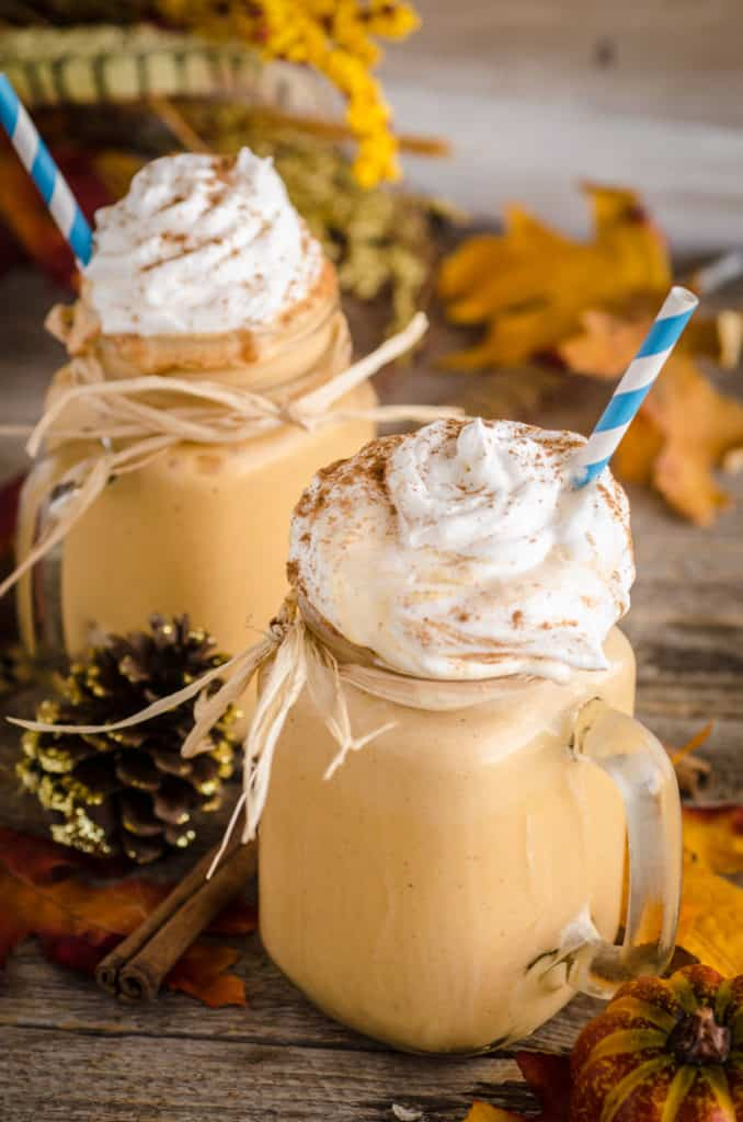 Two Frosty Pumpkin Pie Smoothies sit on a barnwood table surrounded with colorful leaves, shrubbery and a pinecone.