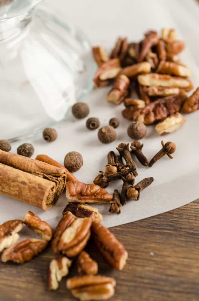 Allspice berries, whole cloves and a cinnamon stick are pictured with chopped pecans for Candied Spice Pecans- The Goldilocks Kitchen