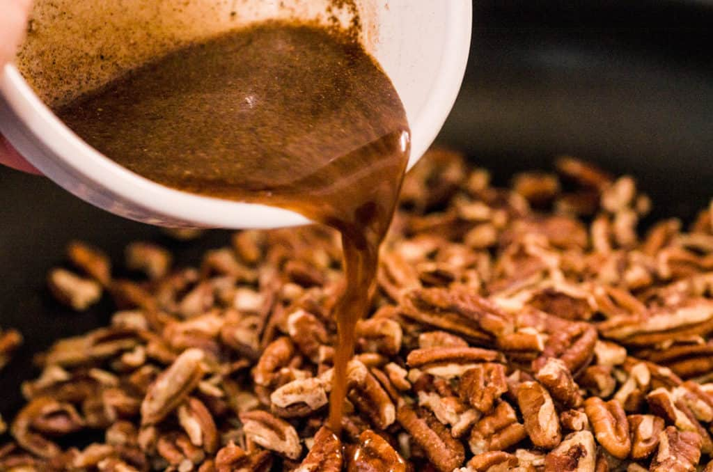 Sugar and spices mixed in water are poured out over a skillet of chopped pecans for Candied Spice Pecans- The Goldilocks Kitchen