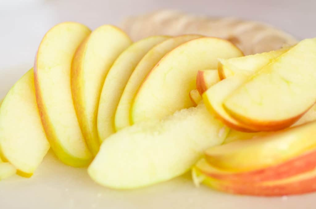Sliced apples sit on a white cutting board ready for Chicken Apple Cheddar Salad. - The Goldilocks Kitchen