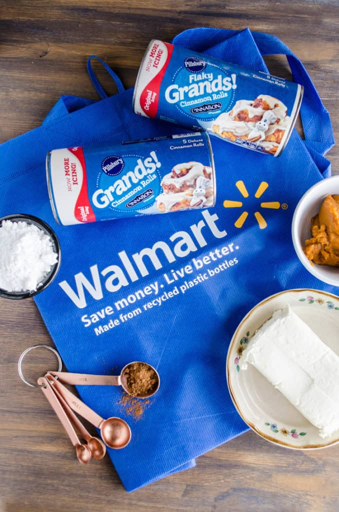 A blue Walmart bag is surrounded by cans of Pillsbury Grands! Cinnamon Rolls Original, pumpkin puree, a brick of cream cheese, powdered sugar and measuring spoons with spice in them to make a Pumpkin Pie Breakfast braid - The Goldilocks Kitchen