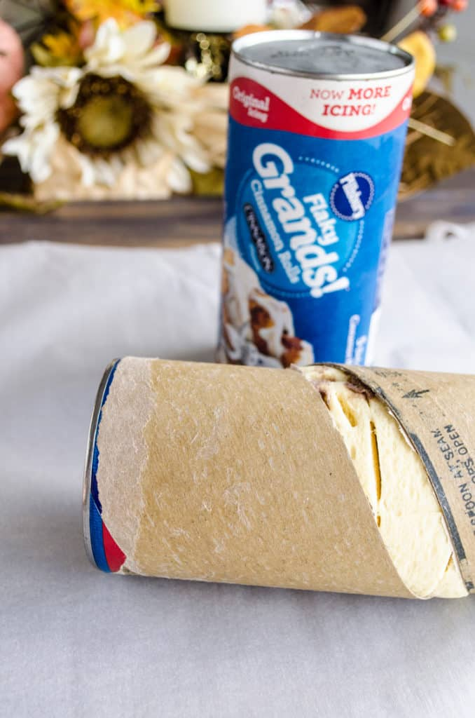 Cans of Pillsbury Grands! Cinnamon Rolls (one opened one not) sit on parchment paper ready to be made into a Pumpkin Pie Breakfast braid - The Goldilocks Kitchen