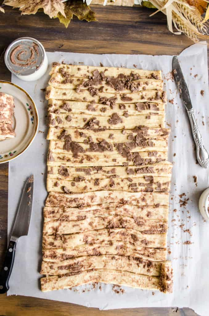 Strips of dough from unrolled cinnamon rolls are lined up to make a Pumpkin Pie Breakfast braid - The Goldilocks Kitchen