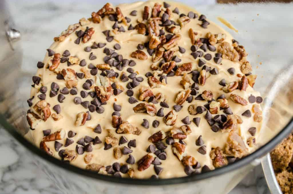 Pecan Pralines are sprinkled over pumpkin cheesecake pudding mix and chocolate chips for Pumpkin Spice Cheesecake Trifle - The Goldilocks Kitchen