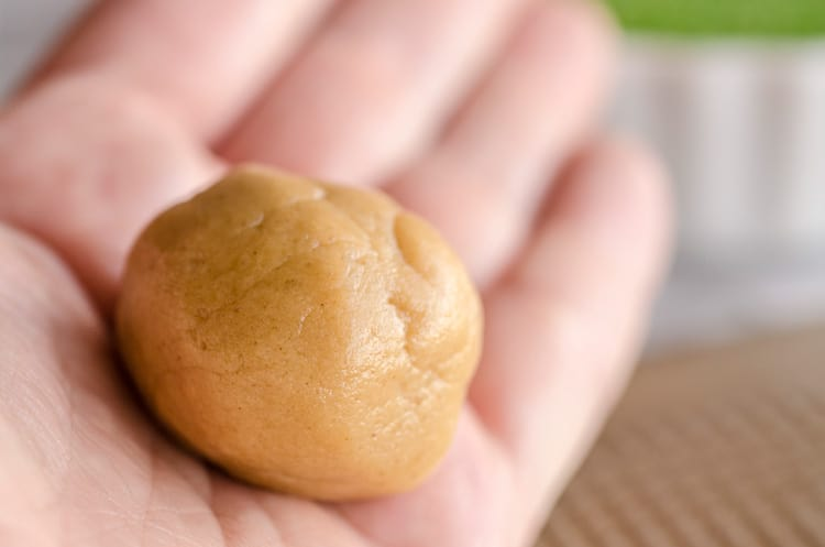 A dough ball sits in the palm of a hand for Dove Peanut Butter Buttons cookies - The Goldilocks Kitchen