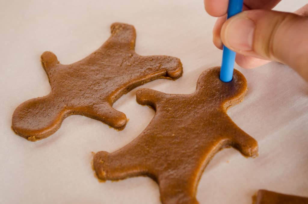 A straw is used to cut a hole in Easy Gingerbread Cookies cut out shapes so they can be hung as ornaments - The Goldilocks Kitchen