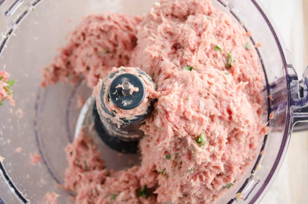 Processed meats and minced fresh parsley fill a food processor bowl for Meatloaf - The Goldilocks Kitchen