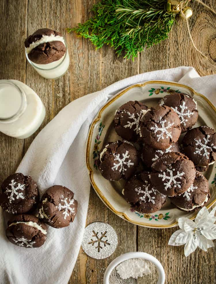 Homemade Oreo Cookies decorated with powdered sugar snowflakes sit on a plate and beside it on a towel next to a bottle of milk - The Goldilocks Kitchen