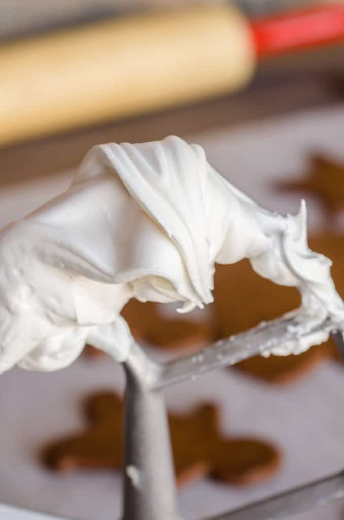 Smooth white Royal Icing Gingerbread Frosting covers a beater from a stand mixer - The Goldilocks Kitchen