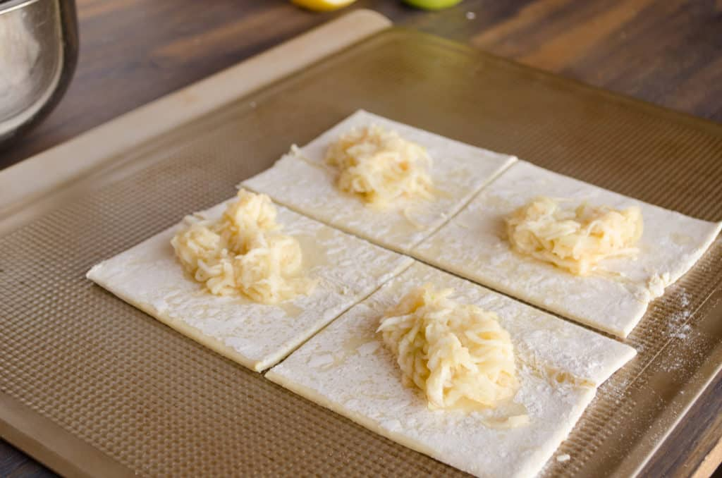 Squares of puff pastry with a small mound of shredded apple in the center are waiting to be folded into Easy Apple Turnovers - The Goldilocks Kitchen
