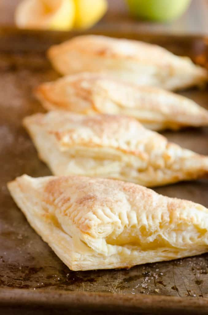 Golden baked Easy Apple Turnovers sprinkled with cinnamon sugar sit in a row on a dark rimmed baking sheet- The Goldilocks Kitchen