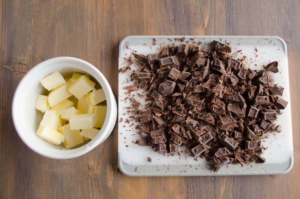 Cubed butter in a white dish and chopped chocolate for making Homemade Chocolate Pudding - The Goldilocks Kitchen